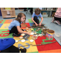 Kacey & Isaac role creating their own dinosaur land using small world resources