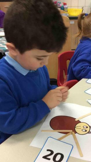 Yakup was able to recognise the numeral 20 and  also count out 20 lolly sticks correctly.