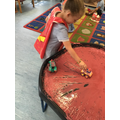 Darcey finds different ways to make marks by using the cars