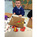 Harley uses his imagination to create his mummy using the tapa shapes