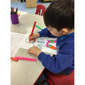 Eli uses good pencil control to trace over the patterns