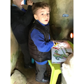 Mason uses the torch to look at books in the cave