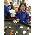 Rebecca explores the loose parts and creates her own model