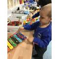 Boris enjoys creating sounds using the xylophone