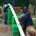 Creating a waterslide outside using guttering and large construction.