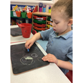 Darcey explored drawing circles with chalks