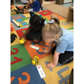 Eva and Lexi working on their directional vocabulary and coding using a Beebot.