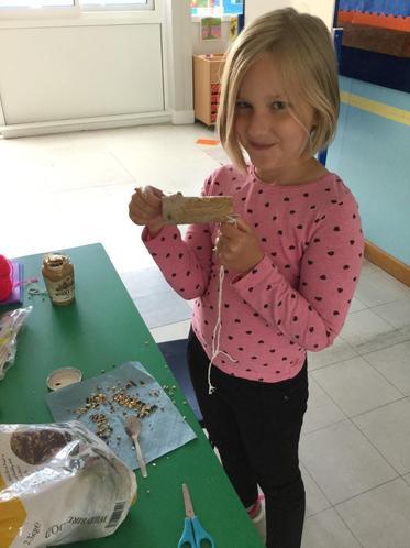 Lena getting messy making a tasty bird feeder!