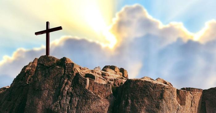 Image of crucifix on a hill with sunbeams