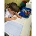 Teddy working hard with his number writing.