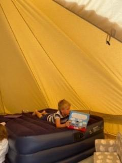 Zavier reads at a very local camp sight.