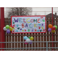 Welcome Back sign and balloons
