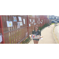 FM putting her pic on the school fence