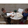 Arlo and Matha writing their spellings in charcoal
