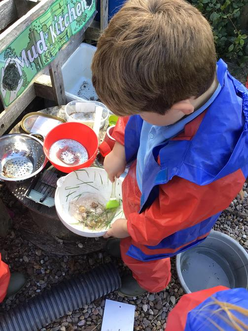 Mixing in the mud kitchen.