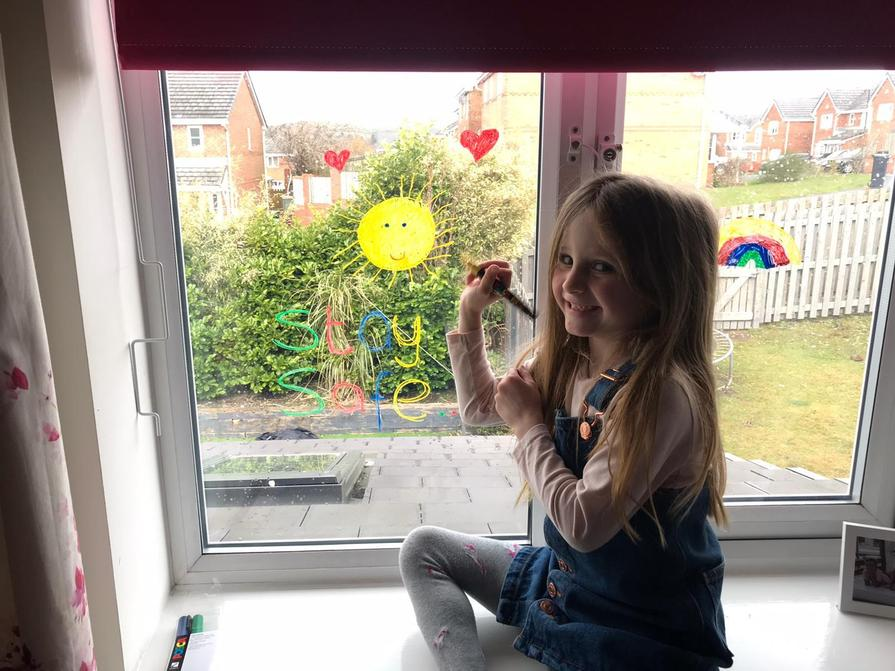 Isabelle adding a sunshine to her window.