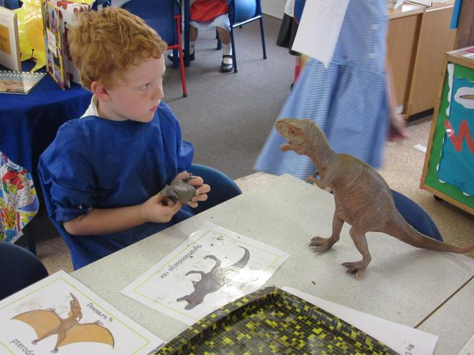Using clay to make dinosaurs.
