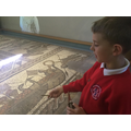 Explaining the story shown by the mosaic.