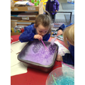 Blowing bubbles to make bubble prints.