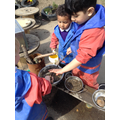 The children work together to stir their soup.