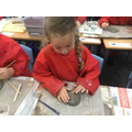 Making clay tiles faces.