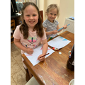 Lilliana colouring flags with her sister.