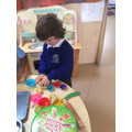 Working on fine motor skills in the dough area.