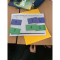 Making the largest number with number cards.