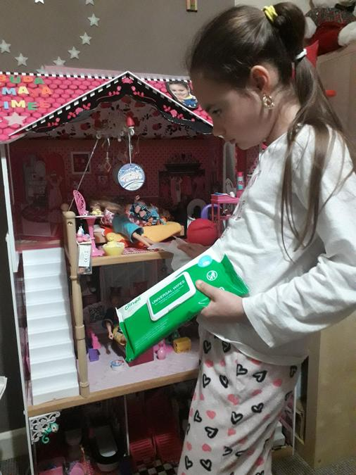 Maya helped by cleaning her dolls' house.