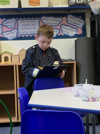 Busy writing a report  in our fire station role play area.