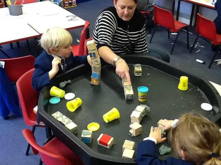 Using playdough to build houses.