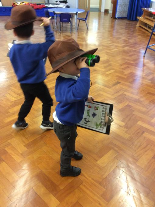 Freddie looked through his binoculars to see the animals.