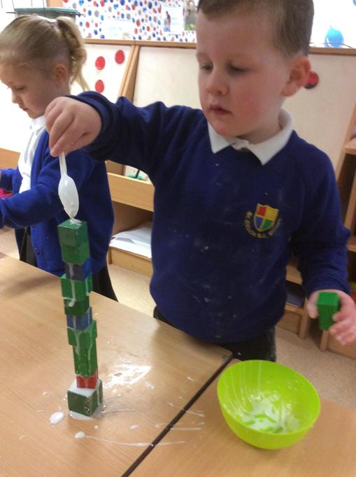Alfred stuck his bricks together to make a tower.