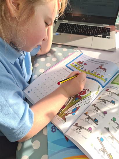Gracie doing EXTRA maths in her work book!