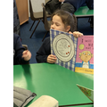 Child reading books with eyes closed.