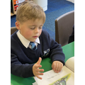 Child reading a book with eyes closed.