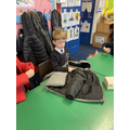 Child trying coat on with eyes closed.