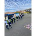 Children doing their coronation walk through the playground.