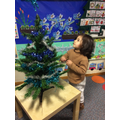 Putting baubles on the tree in our classrrom