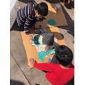 Umair helping his brother make a Volcano