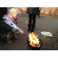 Toasting marshmallows with grown-ups to help us.