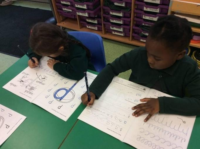 Reception persevering with their handwriting:
