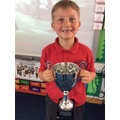 Harry awarded with the trophy for his poetry and time work this week.