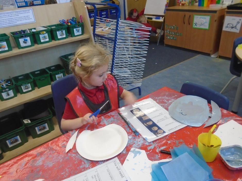 Reading instructions to make a paper plate whale.