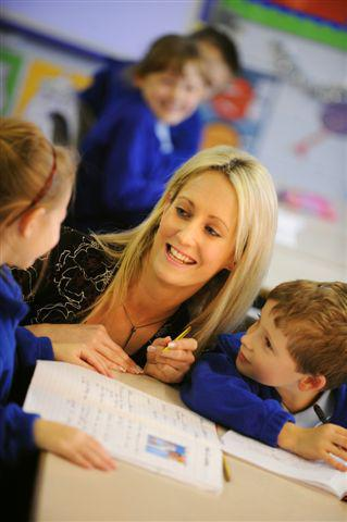 image of teacher smiling whilst working with two children
