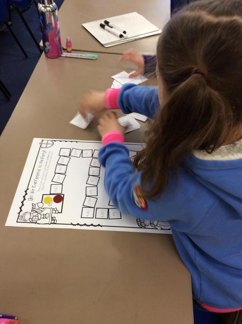 Playing a Sir Cumference place value board game.