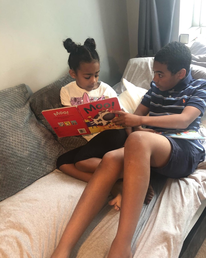 Elsie sharing a book with her brother El-J