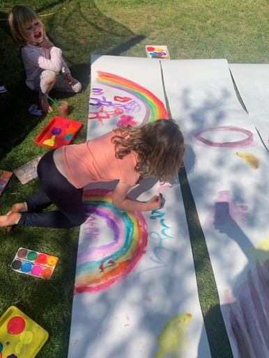 Myla having fun painting a rainbow with Josie