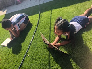 El-J enjoying a book outside with his sister