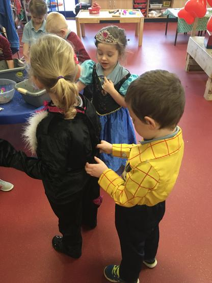 The children help one another to dress up.